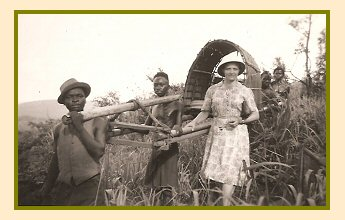 Susie Brucks standing beside the hammock carried by her African porters that she travelled in when going out into the villages in Africa.